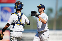 Michigan Wolverines starting pitcher Karl Kauffmann (37) fist bumps catcher Harrison Salter (11) during a game against Army West Point on February 18, 2018 at Tradition Field in St. Lucie, Florida.  Michigan defeated Army 7-3.  (Mike Janes/Four Seam Images)