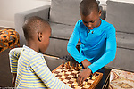 Two brothers, ages 7 and 9, playing chess together at home, 9 year old helping 7 year old with strategy