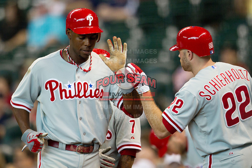 Philadelphia Phillies outfielder John Mayberry #15 is greeted by Nate Schierholtz #22 after he scored in the eighth inning of the Major League baseball game against the Houston Astros on September 16th, 2012 at Minute Maid Park in Houston, Texas. The Astros defeated the Phillies 7-6. (Andrew Woolley/Four Seam Images).