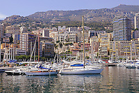 Luxury yachts and boats in Monaco harbor. Mountains and buildings.