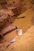 Ouro Verde, Brazil. Young boy garimpeiro (prospector) with pan panning for gold in an illegal gold mine - garimpo.
