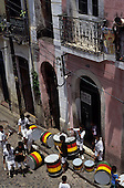 Salvador, Brazil. Olodum drum band with green, red, yellow and black drums preparing to play in colonial Pelourinho.