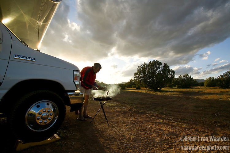 A man grills a steak on an outdoor barbeque while on vacation in Northern Arizona, United States of America. (backlit)