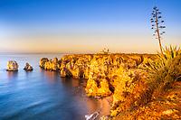 Beautiful, golden sunrise light over the Atlantic Ocean shores, famous Ponta da Piedade cliffs and its lighthouse, in Algarve region, Portugal Europe