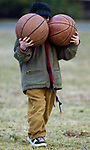 2/15/96--John Ireland, age 6 carries 2 basketballs to the park across from his Trenton Ave home in Pt. Pleasant to play with his friends.