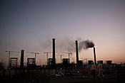 Chinese workers return after work. In the background is the under construction Adani Power plant of 4620 MW capacity in Mundra port industrial city of Gujarat, India. Indian power companies have handed out dozens of major contracts to Chinese firms since 2008. Adani Power Ltd have built elaborate Chinatowns to accommodate Chinese workers, complete with Chinese chefs, ping pong tables and Chinese television. Chinese companies now supply equipment for about 25% of the 80,000 megawatts in new capacity.