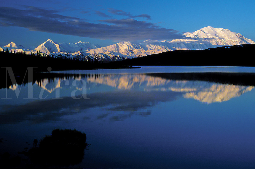 Landscape of Mount McKinley reflected on Wonder Lake. Color contrast in blue of sky, white of mountains and black coastline. Denali National Park, Alaska.