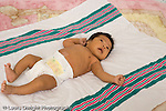 newborn baby girl one month old  Mexican American portrait full length lying on receiving blanket in diaper horizontal reflex tonic neck fencing