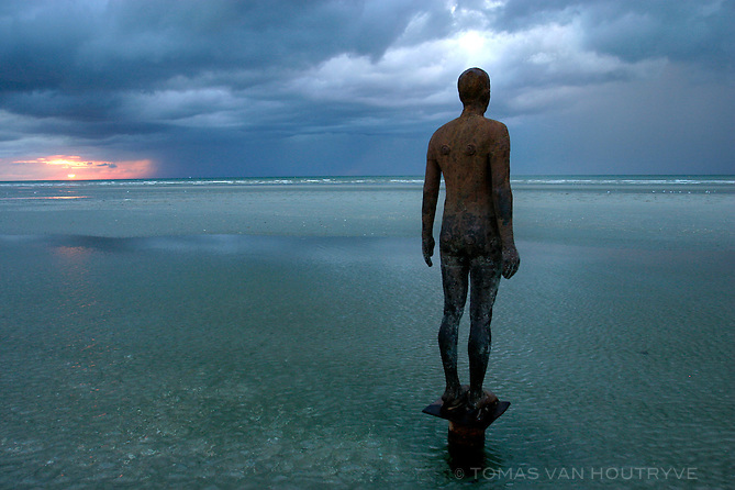 An iron statue created by artist Antony Gormley faces the North Sea in De Panne, Belgium on 30 August, 2003. Gormley placed 100 such statues along the beach in Belgium during the summer of 2003.<br />