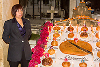 Oaxaca, Mexico, North America.  Day of the Dead Celebrations.  Altar in Memory of Women who have died as Victims of Domestic Violence, San Miguel Cemetery.  Bread of the Dead (Pan de Muertos). The large loaf in the middle with the large knife is for the unknown victims.  The smaller loaves represent victims identified by name.