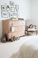 A collection of antique illustrations hangs on the wall above this antique chest of drawers in the master bedroom