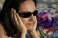Portrait of a woman wearing sunglasses at the beach.