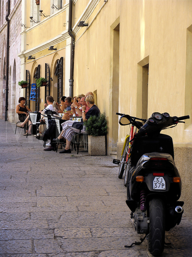 People relaxing at sidewalk tables outside bar on Via San Francesco in Assisi, Ital