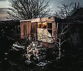 Vor dem Haus von Lilia und Volodymir liegt direkt der Frontabschnitt mit Schützengräben. Ihr Haus war starkem Beschuss ausgesetzt, alle Wände sind durch Schrapnell gelöchert, die großen Fenster haben sie irgendwann nicht mehr ausgetauscht und verdunkelt, um weniger sichtbar zu sein. Auch jetzt sind in regelmäßigen Abständen Granatenexplosionen zu hören.