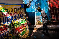 An Afro-Colombian man walks around the wall, covered with Champeta music propaganda, in the market of Bazurto in Cartagena, Colombia, 16 December 2017. Far from the touristy places in the walled city, a colorful, vibrant labyrinth of Cartagena's biggest open-air market sprawls to the Caribbean seashore. Here, in the dark and narrow alleys, full of scrappy stalls selling fruit, vegetables and herbs, meat and raw fish, with smelly garbage on the floor and loud reggaeton music in the air, the African roots of Colombia are manifested.