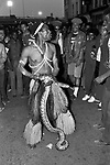 Notting Hill Carnival man dressed in 'black African costume with live stack entertaining a crowd of carnival goers. 1980s UK 1981