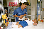 Staff nurse in childrens ward at Alder Hey Hospital Manchester  NHS hospital. UK England Nurse with baby in cot. 1988