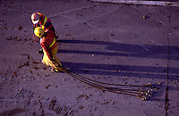 Overview of two road workers, casting long shadows as they walk.
