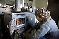 Young man lighting fire in stove of a cabin in Haleakala National Park