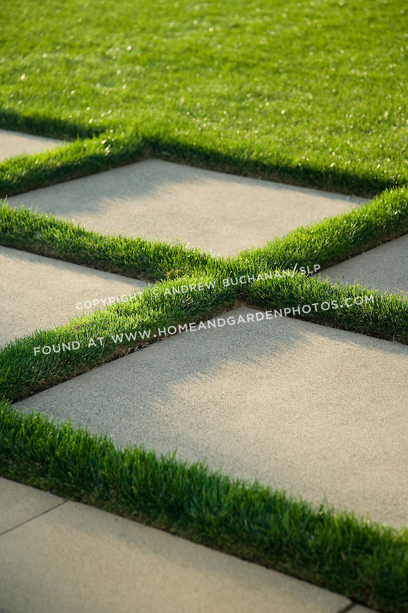 Close up detail of a beautifully manicured, poolside landscape featuring geometrically patterned concrete pavers intersperced with lush green grass lawn glowing in the low angle sunshine in a suburban community east of Seattle.