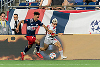 FOXBOROUGH, MA - JULY 7: Yeferson Soteldo #30 of Toronto FC dribbles down the wing as Brando Bye #15 of New England Revolution defends during a game between Toronto FC and New England Revolution at Gillette Stadium on July 7, 2021 in Foxborough, Massachusetts.