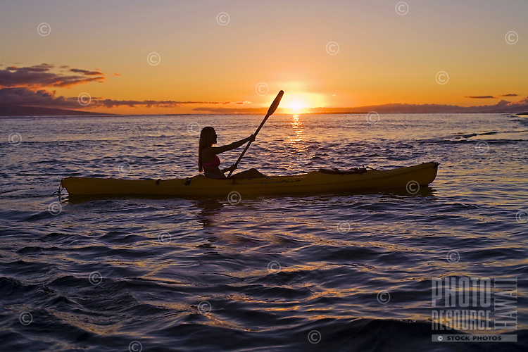 A female paddles a yellow kayak at sunset at Lahaina, Maui.