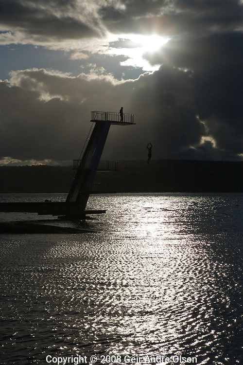 Man jumping from tower at the beach Ingierstrand outside of Oslo, Norway