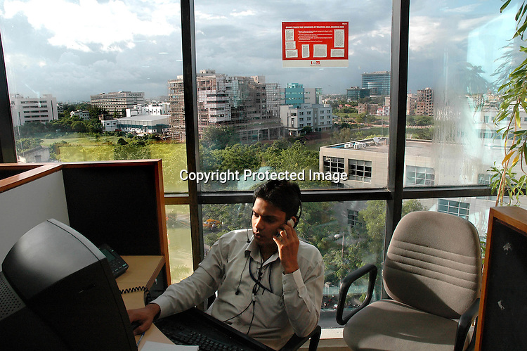 An Indian  Excutive at his deskusing a mobile phone.  Infinity Infotech Park, Saltlake, Kolkata, India  Arindam Mukherjee