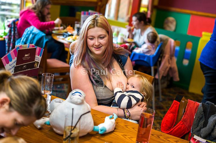 A mother sitting at a table breastfeeds her two year old daughter with her twelve week old baby asleep in a sling on her back.in the family restaurant and play area of a pub.<br /> <br /> Lancashire, England, UK<br /> <br /> Date Taken:<br /> 07-01-2015<br /> <br /> © Paul Carter / wdiip.co.uk