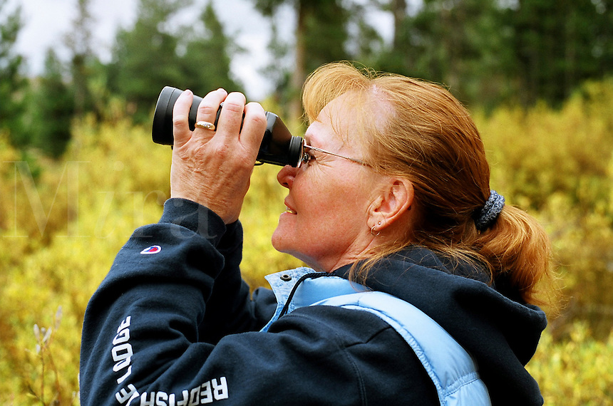 Mature woman looking through binoculars, side view..MR