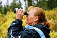 Mature woman looking through binoculars, side view..MR