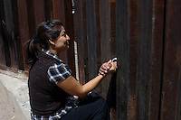 A Mexican woman holds the hand of her husband through an aberture of the fence separating the city of  Nogales, Sonora, in North Mexico, with the USA. The man have been working illegaly in the US for 9 years while his family remains in Mexico.