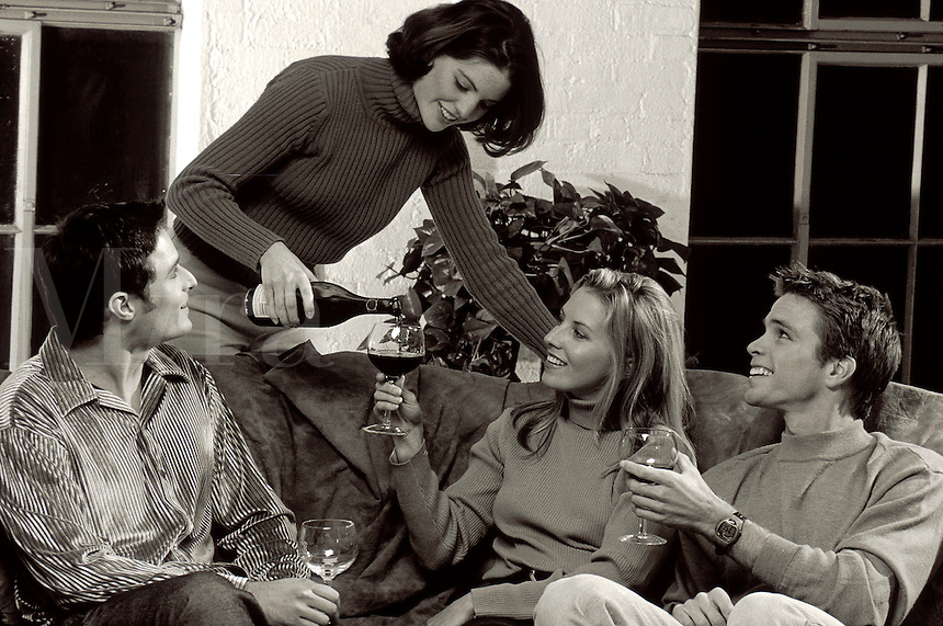 Smiling young couples socializing while relaxing and drinking wine.