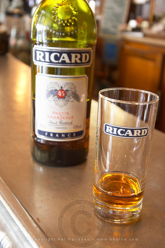 A bottle of Ricard 45 pastis and a glass on a zinc bar in a cafe bar in Paris Pastis is a spirit high alcohol drink flavoured flavored with herbs such as anise (badiane, anis étoilé etoile) and other spices. It is sometimes called pastis or Absinth absinthe. It is served in a tall glass with ice and you pour water on it. It gets cloudy milky when water is added. It is a favourite drink aperitif in Provence Southern France. The Bistrot du Peintre is an old fashioned Paris café cafe bar restaurant of art nouveau design with polished brass, mirrors and old signs