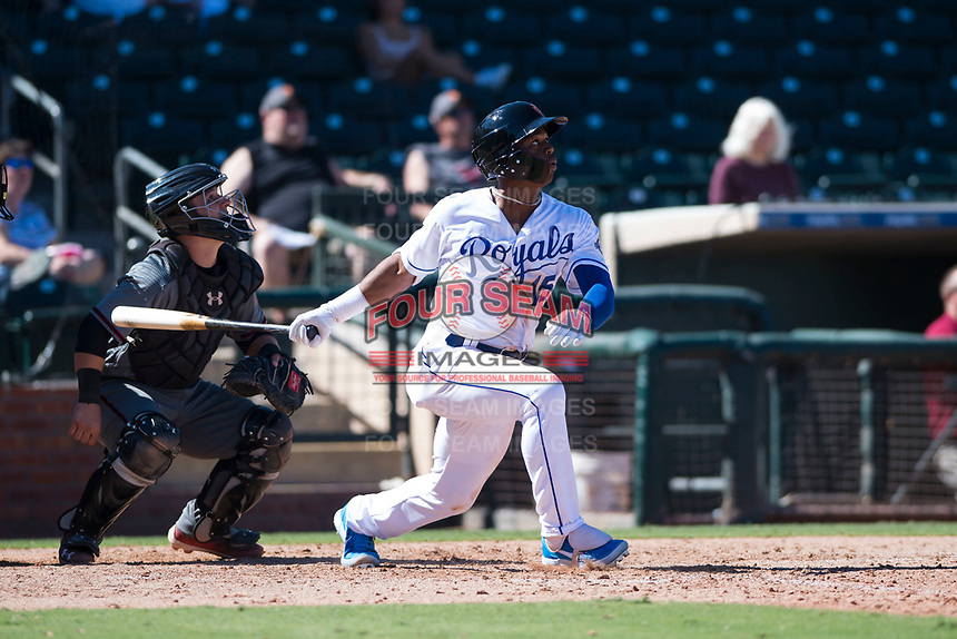 Surprise Saguaros center fielder Khalil Lee (15), of the Kansas City Royals organization, follows through on his swing in front of catcher Daulton Varsho (8) during an Arizona Fall League game against the Salt River Rafters on October 9, 2018 at Surprise Stadium in Surprise, Arizona. Salt River defeated Surprise 10-8. (Zachary Lucy/Four Seam Images)