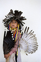 Gallup Navaho Indian Reservation, New Mexico, USA, 2005. hildren dressed in traditional costumes for the new years pow wow celebration. Their harsh reality is that most who live on the reservations now live below the poverty line. Many hogans have no running water or electricity. Jobs in the vicinity are scarce and alcoholism runs rampant. Vehicles have a difficult time accessing the harsh snow covered plains so many families hunker down in cheap hotels in town for the winter. Still, the Navaho tribes try to cling to some semblance of their culture and instill a sense of identity into their children.