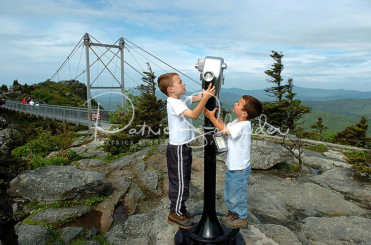 Two young boys check out a viewing telescope at the swing bridge atop Grandfather Mountain in the Blue Ridge Mountains of North Carolina.