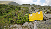 Hiker warning sign along the Appalachian Trail near Lakes of the Clouds in the White Mountains, New Hampshire USA during the summer months. Mount Washington is in the background.