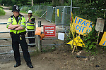 """Balcombe West Sussex UK. Police ans security guards, guard the Cuadrilla Resources site entrance, where Fracking is planned. The sign """"Danger Fire Arms in Use"""", refers to game shooting on the Balcombe Estate."""