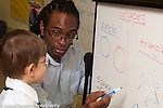 Education Elementary School male teacher working with boy on math, geometric shapes on dry erase board