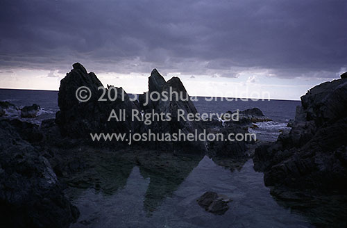 Stormy clouds over rocky shoreline<br />