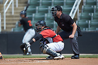 Kannapolis Intimidators catcher Michael Hickman (30) receives a pitch as home plate umpire Colin Baron looks on during the game against the Delmarva Shorebirds at Kannapolis Intimidators Stadium on May 19, 2019 in Kannapolis, North Carolina. The Shorebirds defeated the Intimidators 9-3. (Brian Westerholt/Four Seam Images)
