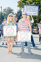 """People hold anti-vaccine signs reading """"Open it up / Business is dying"""" as alt-right organization Super Happy Fun America demonstrates against facemasks, vaccines, and pandemic closures, and in support of the reelection of President Donald J. Trump near the residence of Massachusetts governor Charlie Baker in Swampscott, Massachusetts, on Sat., Sept. 26, 2020. Super Happy Fun America is most well known for organizing the Straight Pride Parade in Boston on August 31, 2019."""