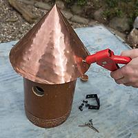 Ein Stück einer Tonröhre wird umgebaut zum Nistkasten, Vogelnistkasten, Meisenkasten, Deko, Dekoration. Schritt 3: ein Spitzdach aus Kupfer, Kupferblech wird auf den Nistkasten aufgesetzt und fest genietet. Upcycling, Bastelei.