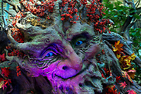 A spooky, colorful smiling face in a tree during an autumn Halloween display in the Bellagio Casino in Las Vegas, Nevada