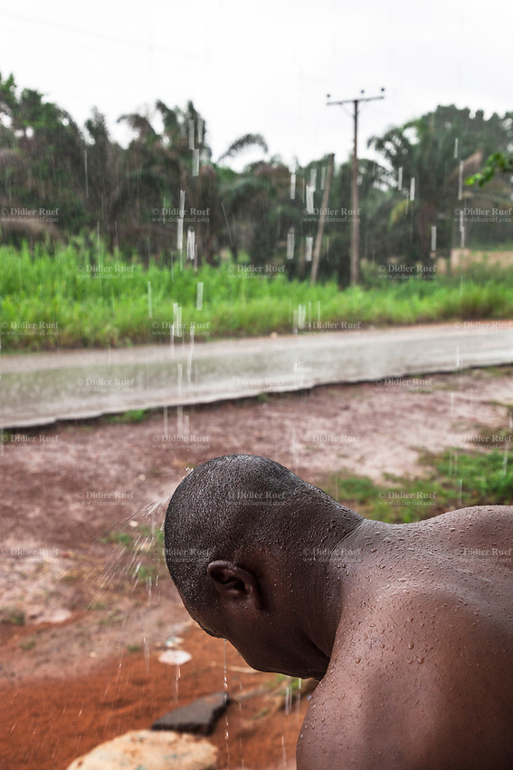 Nigeria. Enugu State. Agbani. Reverend Father Gerald Chukwudi Ani is a catholic priest from the Diocese of Lugano (Ticino, Switzerland). Back in his homeland, he enjoys the feeling of the rain falling on both head and back. Rainy season. Electric pole. 3.07.19 © 2019 Didier Ruef