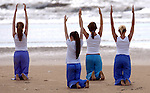 People taking part in an outdoor yoga class on a beach in England