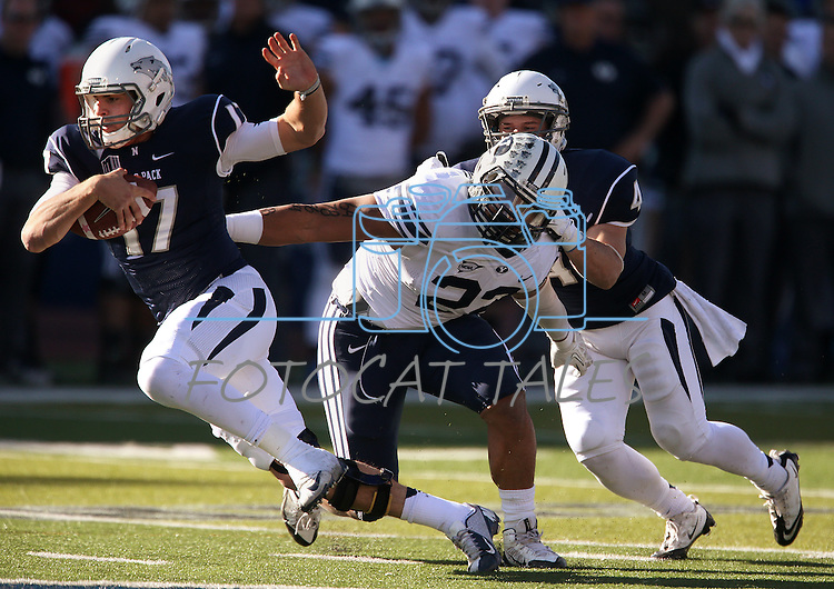 Nevada quarterback Cody Fajardo (17) runs from BYU's Manoa Pikula (22) during the first half of an NCAA college football game in Reno, Nev., on Saturday, Nov. 30, 2013. (AP Photo/Cathleen Allison)