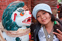 Bodhnath, Nepal.  Young Nepali Woman beside Mythical Snow Leopard at Entrance to Buddhist Shrine.