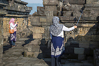 """Borobudur, Java, Indonesia.  Two Young Indonesian Women Photographing the Temple.  The one on the right is using an extension pole to take a """"selfie."""""""